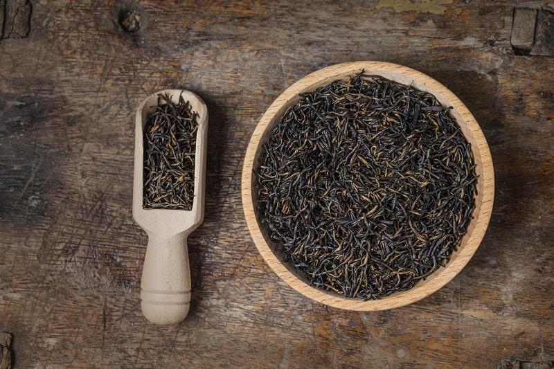 یک کاسه ی چوبی و پیمانه ی چوبی حاوی چای هندی