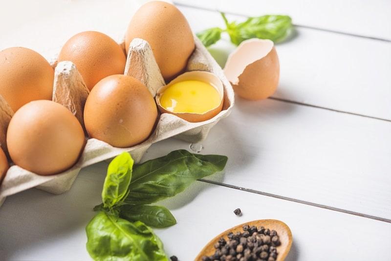 یک شانه تخم مرغ که یکی از تخم مرغ ها شکسته شده و زرده ی آن مشخص است.