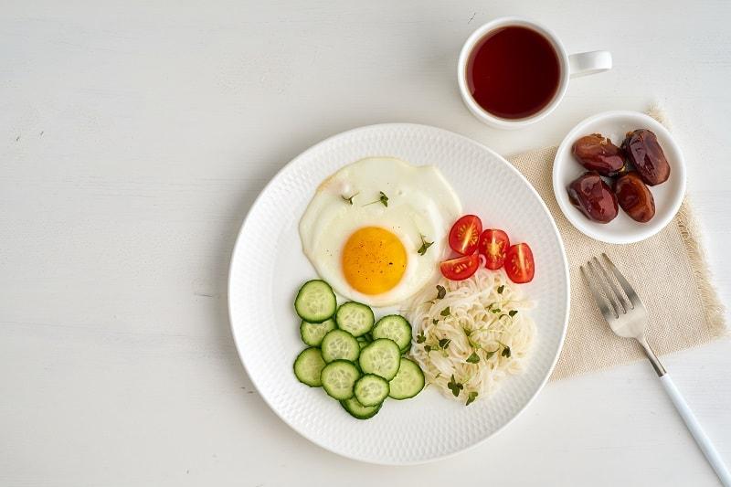 ظرف سفیدی شامل تخم مرغ، خیار، نودالیت و گوجه همراه با مقداری خرما و یک فنجان چای